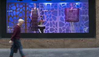 FILE- In this May 16, 2018, file photo a pedestrian makes his way past a window display at Macy's flagship store in New York. Macy's Inc. reports financial results Tuesday, Feb. 26, 2019. (AP Photo/Mary Altaffer, File)
