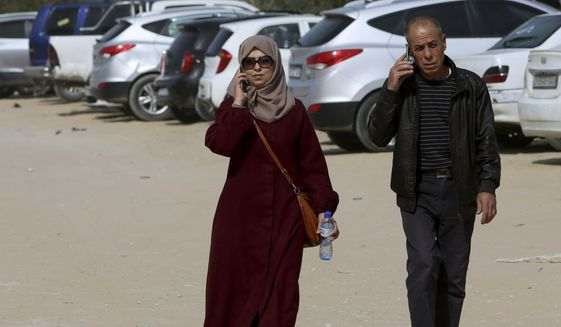 Palestinian journalist Hajar Harb, left, and her father Mohammed, talk on their mobile phones upon their arrival to the court complex in Gaza City, Tuesday, Feb. 26, 2019.  The Gaza journalist is appealing a six-month prison term and fine over her reporting on alleged corruption within the Hamas-run Health Ministry. (AP Photo/Adel Hana)