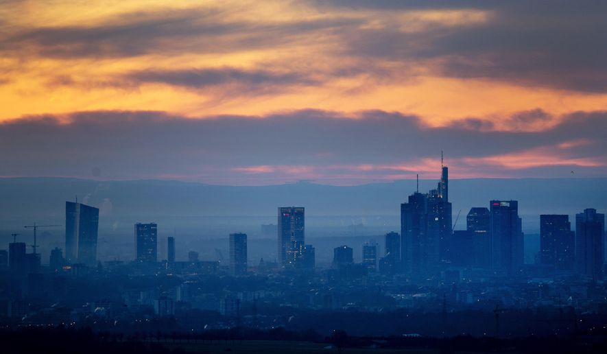 An orange sky is seen over the banking district of Frankfurt, Germany, on Tuesday, Feb. 26, 2019. (AP Photo/Michael Probst)