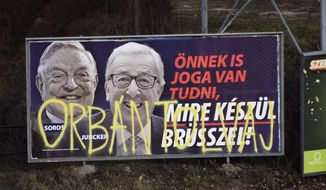 "A billboard from a campaign of the Hungarian government showing EU Commission President Jean-Claude Juncker and Hungarian-American financier George Soros with the caption ""You, too, have a right to know what Brussels is preparing to do."" is displayed at a street in Budapest, Hungary, Feb. 26, 2019. The Hungarian government claims that EU leaders like Juncker, backed by Soros, want to bring mass migration into Europe. The billboard has been sprayed with graffiti saying ""Orban thief,"" in reference to Hungarian Prime Minister Viktor Orban. (AP Photo/Pablo Gorondi)"