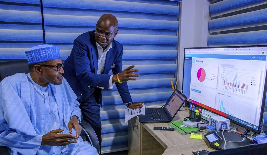 In this photo released by the Nigeria State House, Nigeria Incumbent President Muhammadu Buhari, left, listen to Director of Election Planning and Monitoring Babatunde Raji Fashola, right, as he explain the progress of the party election results in Abuja, Nigeria Monday, Feb. 25, 2019. Nigeria's electoral commission on Monday began announcing official results from the country's 36 states as President Muhammadu Buhari seeks a second term. (Bayo Omoboriowo/Nigeria State House via AP)