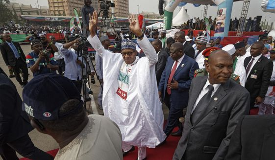 FILE - In this Wednesday, Feb. 13, 2019 file photo, incumbent President Muhammadu Buhari gestures to supporters at a campaign rally in Abuja, Nigeria. Nigeria's president was poised to win a second term in Africa's largest democracy, with unofficial results on Tuesday, Feb. 26, 2019 showing a victory, his campaign spokesman said. (AP Photo/Ben Curtis, File)