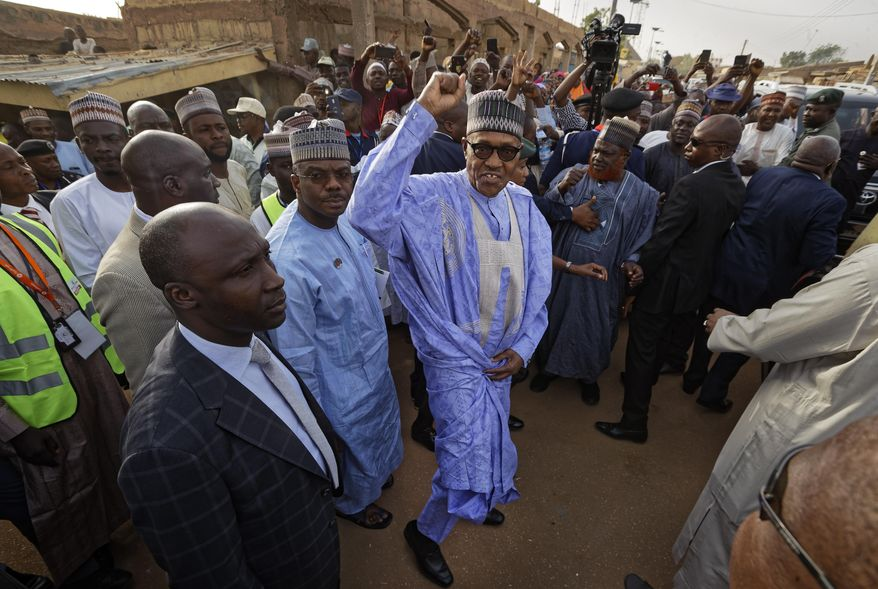 FILE - In this Saturday, Feb. 23, 2019 file photo, Nigeria's President Muhammadu Buhari gestures to supporters after casting his vote in his hometown of Daura, in northern Nigeria. Nigeria's president was poised to win a second term in Africa's largest democracy, with unofficial results on Tuesday, Feb. 26, 2019 showing a victory, his campaign spokesman said. (AP Photo/Ben Curtis, File)