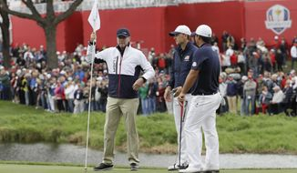 File-This Sept. 28, 2016, file photo shows United States vice-captain Steve Stricker, left, holding a flag for United States' Jordan Spieth and United States' Patrick Reed during a practice round for the Ryder Cup golf tournament at Hazeltine National Golf Club in Chaska, Minn. Stricker called Reed before he was named Ryder Cup captain to clear the air. (AP Photo/David J. Phillip, File)