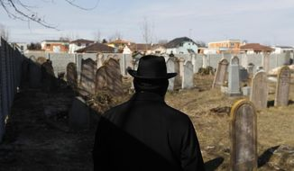 Participant of a conference organized by the Germany-based foundation European Jewish Cemeteries Initiative (EJCI) walks past tombstones at a jewish cemetery near the town of Senec, Slovakia, Tuesday, Feb. 26, 2019. Amid an increase number in the anti-Semitic acts in some European countries, a project has been launched to apply drones and contemporary technology to save Jewish cemeteries in places whose original Jewish population was wiped out in the Holocaust. (AP Photo/Petr David Josek)