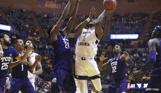 West Virginia forward Derek Culver (1) shoots while defended by TCU center Kevin Samuel (21) during the second half of an NCAA college basketball game Tuesday, Feb. 26, 2019, in Morgantown, W.Va. (AP Photo/Raymond Thompson)