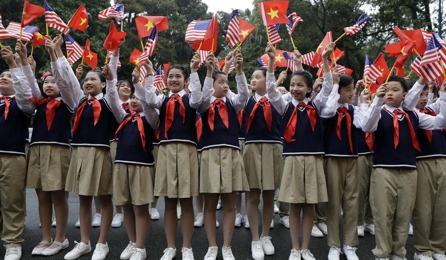 Children wave flags before President Donald Trump arrives to meet Vietnamese President Nguyen Phu Trong at the Presidential Palace, Wednesday, Feb. 27, 2019, in Hanoi. (AP Photo/ Evan Vucci)
