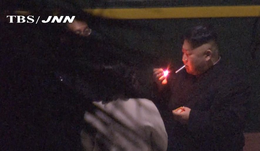 In this image made from Japan's TBS TV video on early Tuesday, Feb. 26, 2019, North Korean leader Kim Jong Un, a habitual smoker, takes a pre-dawn smoke break at the train station in Nanning, China, hours before his arrival in Vietnam for his high-stakes summit with President Donald Trump over resolving the international standoff over the North's nuclear weapons and missiles. (TBS-JNN via AP)