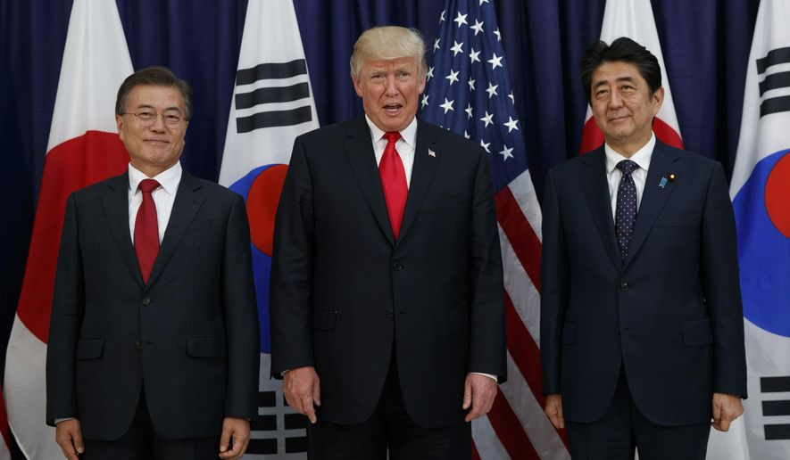 In this July 6, 2017, file photo, U.S. President Donald Trump, center, stands with Japanese Prime Minister Shinzo Abe, right, and South Korean President Moon Jae-in before the Northeast Asia Security dinner at the U.S. Consulate General Hamburg, in Hamburg. (AP Photo/Evan Vucci, File)