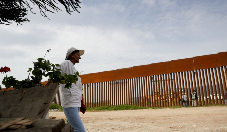 In this Feb. 26, 2019, photo, Mariana Palacios looks towards the border wall separating San Diego from her home in Tijuana, Mexico.  (AP Photo/Gregory Bull)
