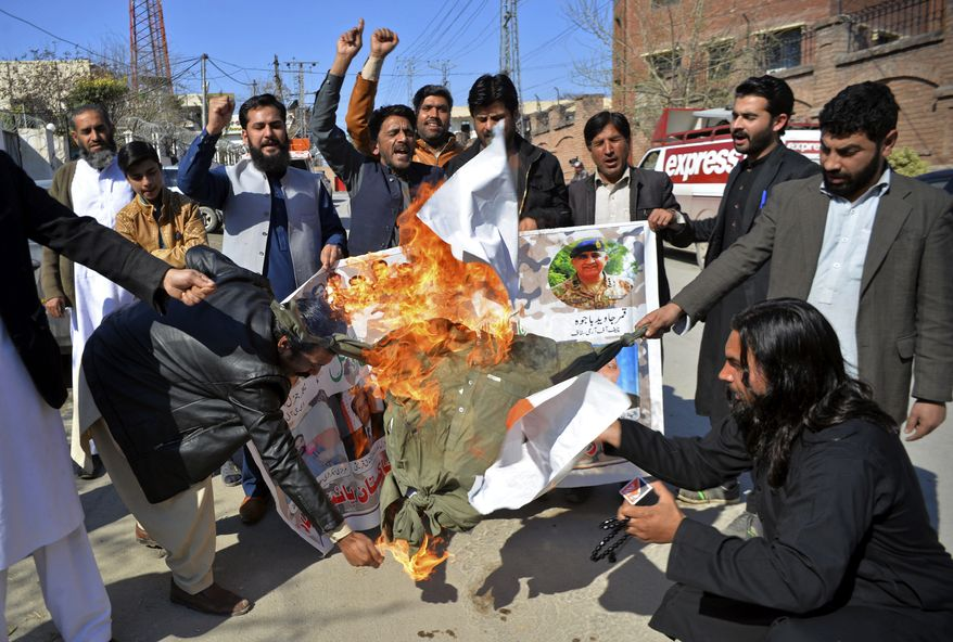Pakistani protesters burn an effigy of Indian Prime Minister Narendra Modi during a rally in Peshawar, Pakistan, Wednesday, Feb. 27, 2019. Pakistan's military said Wednesday it shot down two Indian warplanes in the disputed region of Kashmir and captured two pilots, raising tensions between the nuclear-armed rivals to a level unseen in 20 years. (AP Photo/Muhammad Sajjad)