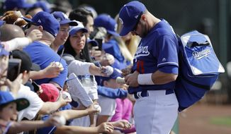 Los Angeles Dodgers' A.J. Pollock signs autographs before a spring training baseball game against the Los Angeles Angels, Sunday, Feb. 24, 2019, in Glendale, Ariz. (AP Photo/Darron Cummings)