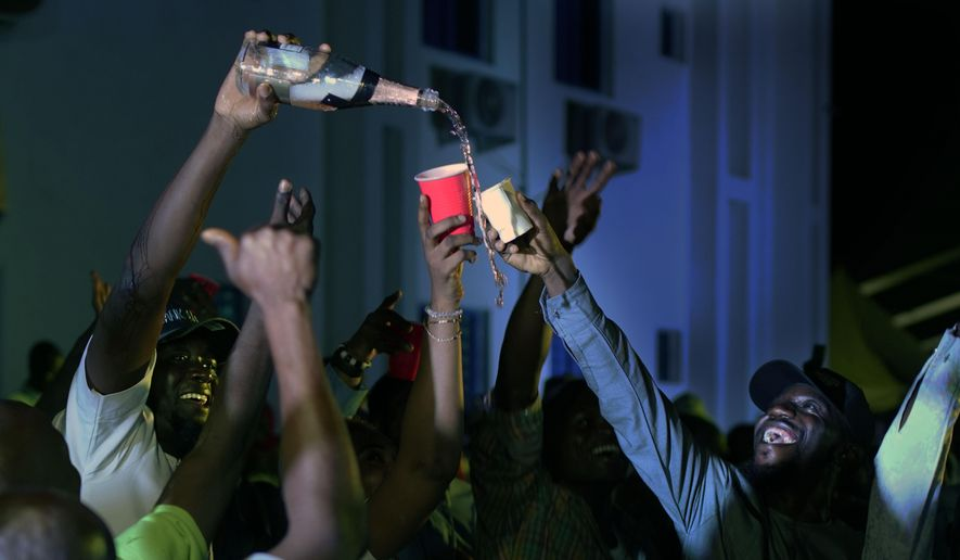 Supporters of Incumbent President Muhammadu Buhari pour champagne anticipating a win as they wait for the results to be officially announced in Abuja, Nigeria, Tuesday, Feb. 26, 2019. Anxious Nigerians on Tuesday awaited a second day of state-by-state announcements of presidential election results in a race described as too close to call. Buhari is facing opposition presidential candidate Atiku Abubakar. (AP Photo/Jerome Delay)