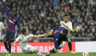 Barcelona forward Lionel Messi, right, is tackled by Real midfielder Luka Modric during the Copa del Rey semifinal second leg soccer match between Real Madrid and FC Barcelona at the Bernabeu stadium in Madrid, Spain, Wednesday Feb. 27, 2019. (AP Photo/Andrea Comas)