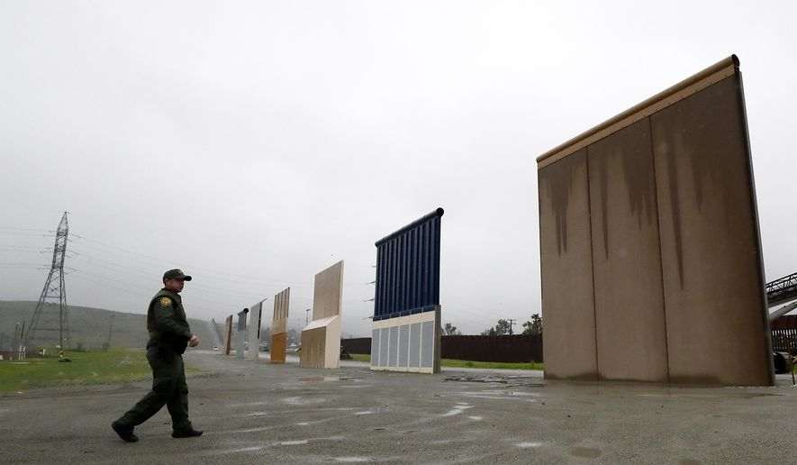 FILE - In this Feb. 5, 2019 file photo a Border Patrol agent walks towards prototypes for a border wall in San Diego. The Trump administration on Wednesday, Feb. 27 plans to demolish eight prototypes of the president's prized border wall that the government built near San Diego one year ago. (AP Photo/Gregory Bull,File)