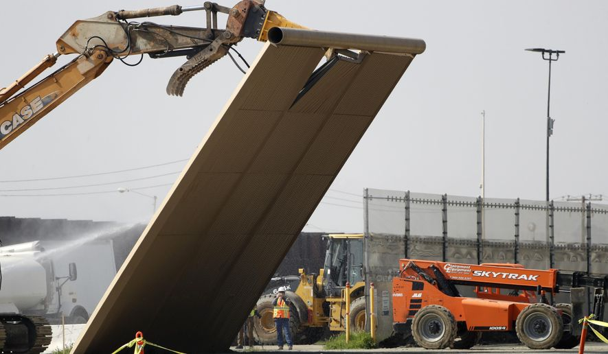 A border wall prototype falls during demolition at the border between Tijuana, Mexico, and San Diego, Wednesday, Feb. 27, 2019, in San Diego. The government is demolishing eight prototypes of Donald Trump's prized border wall that instantly became powerful symbols of his presidency when they were built nine months after he took office. (AP Photo/Gregory Bull)