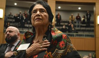 """Dolores Huerta, 88, the Mexican-American social activist who formed a farmworkers union with Cesar Chavez, stands for the Pledge of Allegiance in Spanish while visiting the New Mexico Statehouse on Wednesday, Feb. 27, 2019. The New Mexico-born Huerta was honored by the House for """"Dolores Huerta Day"""" as lawmakers work to save her birthplace in Dawson, New Mexico. (AP Photo/Russell Contreras)"""