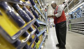 FILE- In this Feb. 23, 2018, file photo sales associate Larry Wardford, of Holliston, Mass., places items on selves at a Lowe's retail home improvement and appliance store, in Framingham, Mass. Lowe's Companies, Inc. reports financial results Wednesday, Feb. 27, 2019. (AP Photo/Steven Senne)