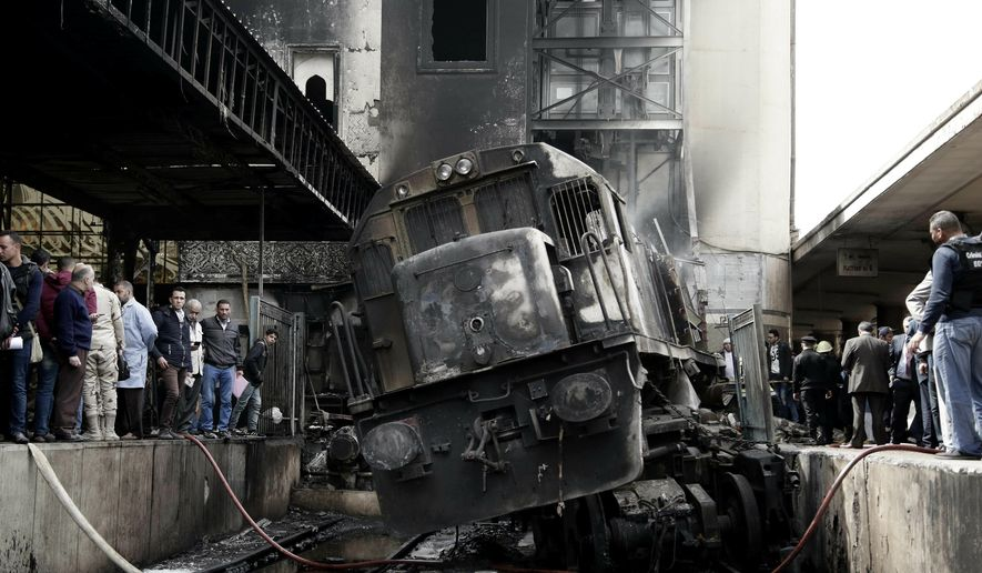 People look at a damaged train inside Ramsis train station in Cairo, Egypt, Wednesday, Feb. 27, 2019. An Egyptian medical official said at least 20 people have been killed and dozens injured after a railcar rammed into a barrier inside the station causing an explosion of the fuel tank and triggering a huge blaze that engulfed that part of the station. The head of the Cairo Railroad Hospital said the death toll is expected to rise further. (AP Photo/Nariman El-Mofty)