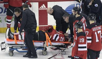 New Jersey Devils defenseman Mirco Mueller is wheeled off the ice on a stretcher after being injured during the third period of an NHL hockey game against the Calgary Flames Wednesday, Feb. 27, 2019, in Newark, N.J. The Flames defeated the Devils 2-1.(AP Photo/Bill Kostroun)