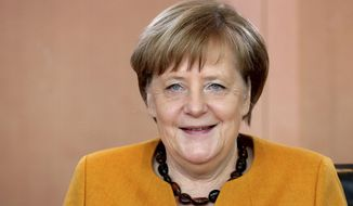 German Chancellor Angela Merkel smiles as she arives for the weekly cabinet meeting at the Chancellery in Berlin, Germany, Wednesday, Feb. 27, 2019. (AP Photo/Michael Sohn)