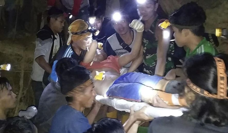 In this undated photo released by Indonesian Search And Rescue Agency (BASARNAS) rescuers evacuate a survivor from a collapsed gold mine in Bolaang Mongondow, North Sulawesi, Indonesia. The collapse of an unlicensed gold mine in Indonesia's North Sulawesi province has buried dozens of people, a disaster official said Wednesday, Feb. 27, 2019, as emergency personnel used their bare hands and farm tools in a desperate attempt to reach victims calling for help from beneath the rubble. (BASARNAS via AP)