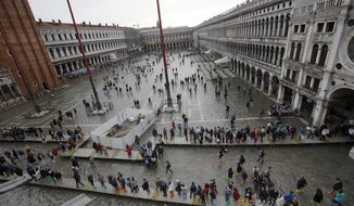 FILE - In this Thursday, Nov. 1, 2018 file photo, tourists walk in flooded St. Mark's Square in Venice, Italy. Venice's city council late Tuesday, Feb. 26, 2018, approved a visitors tax on day-trippers, aimed at paying for essential services that are more costly to perform in the lagoon city, such as trash collection and the cleaning of public areas. (AP Photo/Luca Bruno, File)