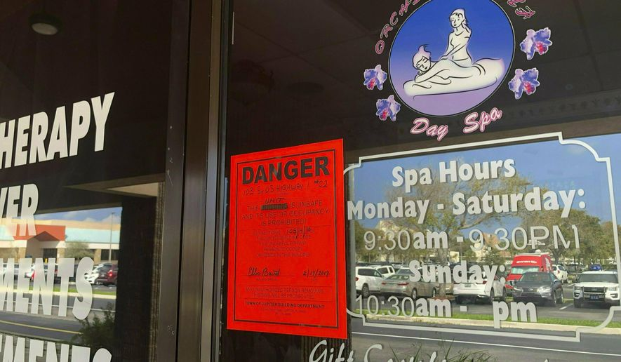 FILE - In this Feb. 19, 2019, file photo, a sign is posted outside of Orchids of Asia Day Spa in Jupiter, Fla., one of several spas closed in south Florida as a result of a six-month investigation into sex trafficking. The Florida prostitution sting that ensnared New England Patriots owner Robert Kraft is a reminder of the human trafficking and abuse taking place behind the darkened windows of many of these storefronts, and how challenging those problems can be to address. (Hannah Morse/Palm Beach Post via AP, File)