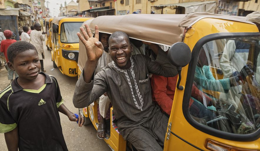 """A supporter of Nigeria's President Muhammadu Buhari holds up four fingers to indicate """"four more years"""", in the streets of Kano, northern Nigeria, Wednesday, Feb. 27, 2019. Buhari was declared the clear winner of a second term in Africa's largest democracy early Wednesday, after a campaign in which he urged voters to give him another chance. (AP Photo/Ben Curtis)"""