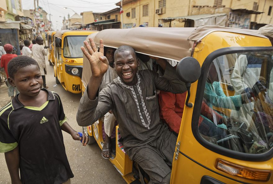 "A supporter of Nigeria's President Muhammadu Buhari holds up four fingers to indicate ""four more years"", in the streets of Kano, northern Nigeria, Wednesday, Feb. 27, 2019. Buhari was declared the clear winner of a second term in Africa's largest democracy early Wednesday, after a campaign in which he urged voters to give him another chance. (AP Photo/Ben Curtis)"