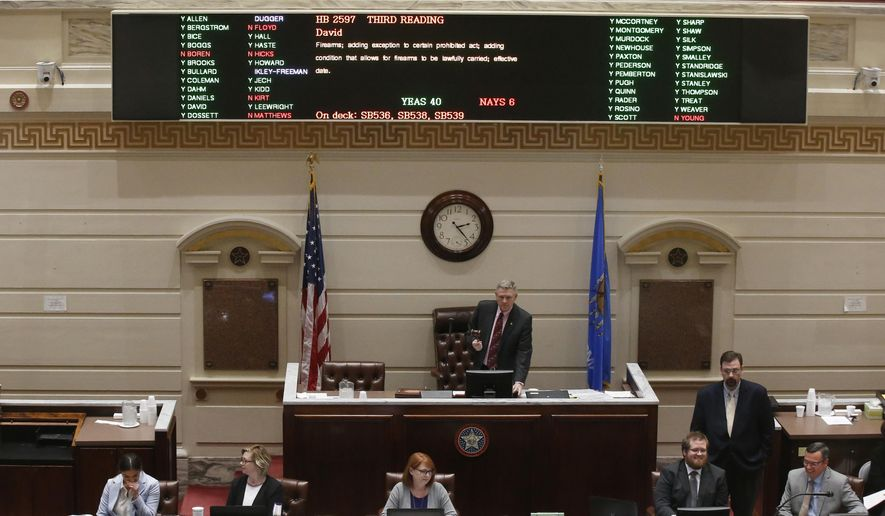 Oklahoma state Sen. Gary Stanislawski, R-Tulsa, stands under the voting board as the vote is counted on the permitless carry bill on the Senate floor Wednesday, Feb. 27, 2019, in Oklahoma City. (AP Photo/Sue Ogrocki)