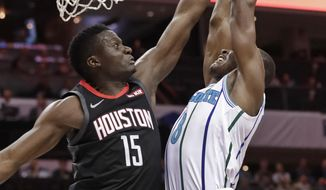 Houston Rockets' Clint Capela (15) blocks a shot by Charlotte Hornets' Bismack Biyombo (8) during the first half of an NBA basketball game in Charlotte, N.C., Wednesday, Feb. 27, 2019. (AP Photo/Chuck Burton)
