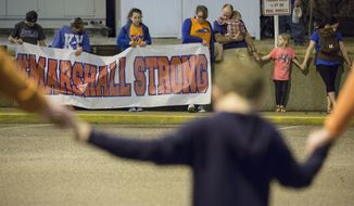 FILE - In this Feb. 15, 2018 file photo people, including students and a classmate who was shot during the Marshall County High School shooting on Jan. 23, attend a vigil for those injured and killed in Wednesday's school shooting in Florida, in downtown Benton, Ky. The Kentucky House of Representatives has passed a school safety bill more than one year after two students were killed in a shooting at a western Kentucky high school, Wednesday, Feb. 27, 2019. (Ryan Hermens/The Paducah Sun via AP, file)