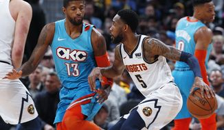 Denver Nuggets guard Will Barton, right, tries to drive past Oklahoma City Thunder forward Paul George during the first half of an NBA basketball game Tuesday, Feb. 26, 2019, in Denver. (AP Photo/David Zalubowski)