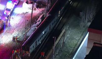 In this image taken from video provided by WNYW-TV, first responders work the scene of a collision between a commuter train and a motor vehicle in Westbury, N.Y., Tuesday, Feb. 26, 2019. Authorities say that three people were killed when the vehicle they were riding in was struck by the Manhattan-bound train. (WNYW-TV via AP)