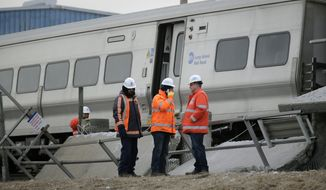 Emergency personnel look over the site of a fatal train collision in Westbury, N.Y., Wednesday, Feb. 27, 2019. Two commuter trains traveling in opposite directions collided with a vehicle on the tracks in Westbury, killing all three occupants in the vehicle before one of the trains derailed and tore into a concrete platform Tuesday night, according to officials. (AP Photo/Seth Wenig)