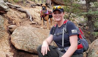 This undated photo provided by her wife Jessica Kibodeaux shows Lindsey Muller and her dog Emma hiking in the Cheyenne Mountains west of Fort Carson, Colo. Muller, a 19-year combat veteran who served multiple tours in Iraq, diligently followed the Pentagon guidelines to transition. In the nearly three years since the U.S. military welcomed transgender people into the armed forces in 2016, they have served without incident. Some, like Muller, have earned prestigious medals or received other forms of recognition. (Jessica Kibodeaux via AP)