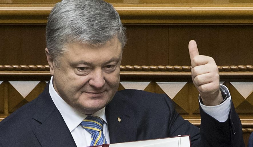 FILE - In this file photo dated Tuesday Feb. 19, 2019, Ukrainian President Petro Poroshenko shows the newly signed Constitutional amendment to joining the EU and NATO in Ukrainian parliament in Kiev, Ukraine.  President Petro Poroshenko said he would instruct his government to formulate a new draft law on punishing officials for corruption and that it would be submitted to parliament as an urgent priority. (Mikhail Palinchak, Presidential Press Service Pool Photo via AP, File)