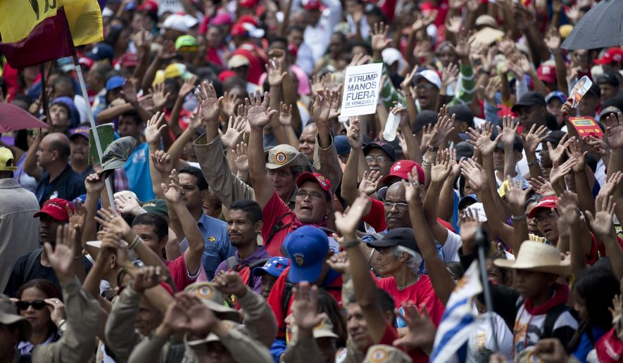 "Supporters of Venezuela's President Nicolas Maduro raise their hands swearing allegiance to the fatherland during an ""anti-intervention"" march coinciding with the anniversary of the deadly 1989 social uprising against neoliberal measures known as the Caracazo, in Caracas, Venezuela, Wednesday, Feb. 27, 2019. (AP Photo/Ariana Cubillos)"