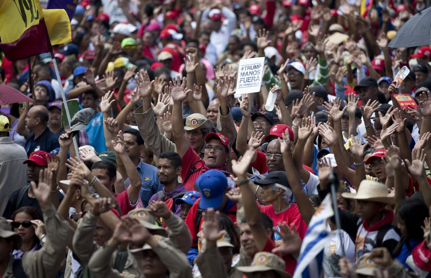"""Supporters of Venezuela's President Nicolas Maduro raise their hands swearing allegiance to the fatherland during an """"anti-intervention"""" march coinciding with the anniversary of the deadly 1989 social uprising against neoliberal measures known as the Caracazo, in Caracas, Venezuela, Wednesday, Feb. 27, 2019. (AP Photo/Ariana Cubillos)"""