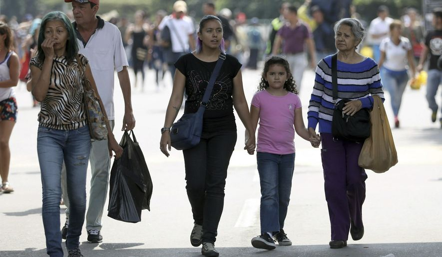 In this Feb. 11, 2019 photo, Venezuelan Diomira Becerra, left center, arrives with her 7-year-old daughter Hillary and her mother Betty Guerrero, for an interview at the entrance of the Simon Bolivar International Bridge, in La Parada, Colombia, near Cucuta. Becerra left Venezuela three years ago and has built a life for her family in the border city of Cucuta. (AP Photo/Fernando Vergara)