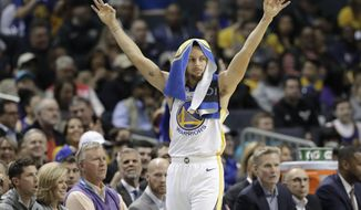 Golden State Warriors' Stephen Curry gestures from the bench after a teammate's basket against the Charlotte Hornets during the first half of an NBA basketball game in Charlotte, N.C., Monday, Feb. 25, 2019. (AP Photo/Chuck Burton)
