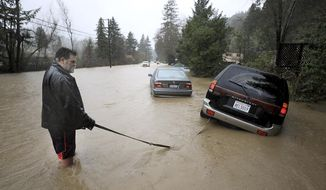 Tim Russell of Guerneville attempts to pull a motorist from Armstrong Woods Road after it became inundated in Guerneville, Calif., Tuesday, Feb. 26, 2019, but Russell became stuck himself. The town of Guerneville and some two dozen other communities are at risk of flooding from the Russian River north of San Francisco, which hit flood stage Tuesday evening and was expected to peak Wednesday morning at more than 46 feet - the highest point in nearly a quarter-century. (Kent Porter/The Press Democrat via AP)