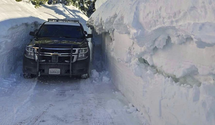 This photo provided by the California Highway Patrol Truckee Division shows a patrol vehicle navigating a stretch of Interstate 80 in the Donner Pass area of the Sierra Nevada, just west of Truckee, Calif., that remained closed Wednesday morning, Feb. 27, 2019. An avalanche has prompted Amtrak officials to suspend passenger rail service between Sacramento and Reno, Nevada after more than more than 4 feet (1.2 meters) of snow fell in the Sierra Nevada. Officials also shut down a 70-mile (112-kilometers) stretch of Interstate 80 from Reno to Colfax, California. (California Highway Patrol via AP)