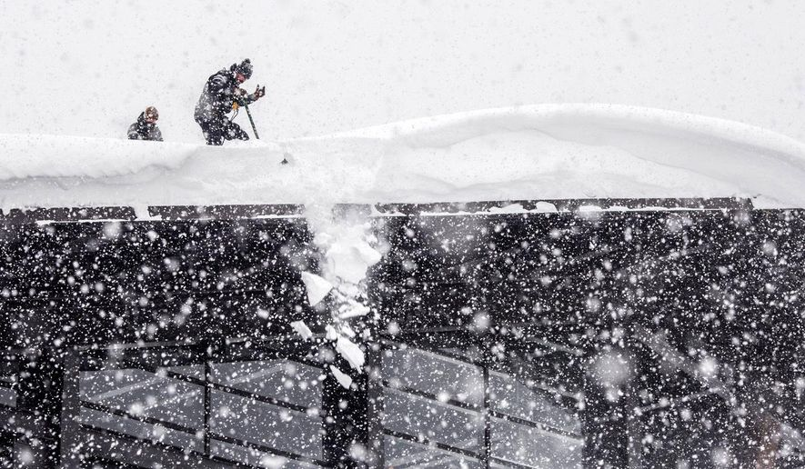 In this Sunday, Feb. 24, 2019 photo, Jackson Hole Mountain Resort employees clear a large, overhanging cornice from the top of the tram dock. Strong winds accompanied the most recent storm that pushed the resort's snowfall total over the 400-inch mark on the season, with more than 14 feet of snowfall measured at the mountain's Rendezvous Bowl plot since Feb. 1. (Ryan Dorgan/Jackson Hole News and Guide via AP)