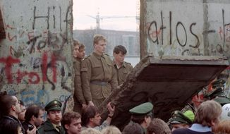 ** PACKAGE TO GO WITH THE 20TH ANNIVERSARY OF THE FALL OF THE BERLIN WALL ** SIX OF TWENTY ** FILE - East German border guards look through a hole in the Berlin wall after demonstrators pulled down one segment of the wall at Brandenburg gate in this Nov. 11, 1989 file picture. Monday, Nov. 9, 2009 marks the 20th anniversary of the fall of the Berlin Wall. (AP Photo/Lionel Cironneau)