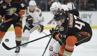 Chicago Blackhawks center Jonathan Toews, upper right, and Anaheim Ducks defenseman Hampus Lindholm vie for the puck during the first period of an NHL hockey game Wednesday, Feb. 27, 2019, in Anaheim, Calif. (AP Photo/Mark J. Terrill)