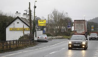 FILE - In this file photo dated Monday, Jan. 30, 2017, a bureau de change on the border between the Irish Republic and Northern Ireland, near the town of Jonesborough, Northern Ireland.  The Motor Insurers' Bureau of Ireland have issued a warning to Irish drivers, Thursday Feb. 28, 2019, that they will need a special insurance document to cross the currently invisible border from Ireland into Northern Ireland, if the U.K. leaves the European Union without a deal. (AP Photo/Peter Morrison, FILE)