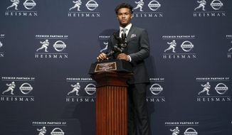 FILE - In this Dec. 8, 2018, file photo, Oklahoma quarterback Kyler Murray poses with the Heisman Trophy after winning the award, in New York. Murray's measurements were among the most anticipated at this year's NFL scouting combine after he spurned the Oakland Athletics and a career in Major League Baseball for a shot at the NFL. (AP Photo/Craig Ruttle, File)
