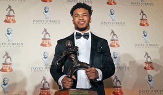 FILE - In this Feb. 18, 2019, file photo, Heisman Trophy winning quarterback Kyler Murray poses with the Davey O'Brien football award, in Fort Worth, Texas. Murray's measurements were among the most anticipated at this year's NFL scouting combine after he spurned the Oakland Athletics and a career in Major League Baseball for a shot at the NFL.  (AP Photo/LM Otero, File)